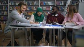 Πολυφυλετικοί σπουδαστές που κάνουν τη μελέτη ομάδας στη βιβλιοθήκη απόθεμα βίντεο