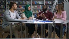 Πολυφυλετικοί φίλοι που εργάζονται στο πανεπιστημιακό πρόγραμμα απόθεμα βίντεο
