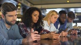 Πολυφυλετικοί φίλοι που τυλίγουν smartphones αγνοώντας ο ένας τον άλλον, εθισμός συσκευών απόθεμα βίντεο