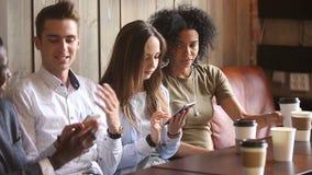 Πολυφυλετικοί φίλοι χρησιμοποιώντας smartphones και μιλώντας στο καφέ, κινητός εθισμός απόθεμα βίντεο