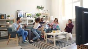 Πολυφυλετικός αθλητισμός προσοχής ομάδας στη TV στο σπίτι ενθαρρυντικ απόθεμα βίντεο