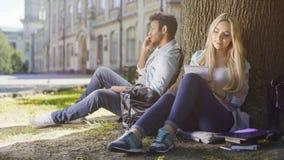 Πολυφυλετικός τύπος που μιλά στο κινητό τηλέφωνο κάτω από το δέντρο, κορίτσι που παίρνει τις σημειώσεις στο σημειωματάριο Στοκ φωτογραφία με δικαίωμα ελεύθερης χρήσης