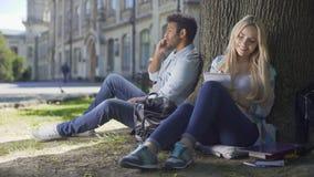 Πολυφυλετικός τύπος που μιλά στο κινητό τηλέφωνο κάτω από το δέντρο, κορίτσι που παίρνει τις σημειώσεις στο σημειωματάριο απόθεμα βίντεο