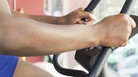 Πολυφυλετικός τύπος που το στάσιμο ποδήλατο που κρατά τα χέρια στη λαβή, καρδιο workout απόθεμα βίντεο