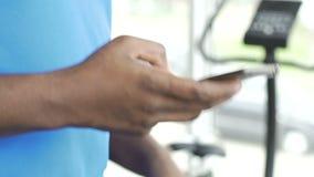 Πολυφυλετικό αρσενικό που χρησιμοποιεί το κινητό τηλέφωνο περπατώντας treadmill στη γυμναστική, διαδρομή app φιλμ μικρού μήκους