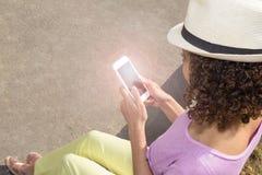 Πολυφυλετικό κορίτσι με τη σγουρή τρίχα που χρησιμοποιεί το smartphone Ζωηρόχρωμος θρόμβος στοκ εικόνες