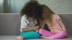 Πολυ-εθνικά παιδιά που κάθονται στον καναπέ και που παίζουν στο smartphone, σύγχρονη τεχνολογία απόθεμα βίντεο