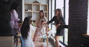 Πολυ εθνικές κυρίες στις πυτζάμες που απολαμβάνουν το χρόνο μαζί ενώ πίνοντας κρασί σε ένα πανοραμικό αστικό ύφος σχεδίου σοφιτών φιλμ μικρού μήκους