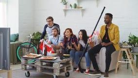 Πολυ εθνική ομάδα αθλητικών ανεμιστήρων φίλων με τις καναδικές εθνικές σημαίες που προσέχει το πρωτάθλημα χόκεϋ στη TV από κοινού φιλμ μικρού μήκους