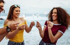 Πολυ-εθνική ομάδα ανθρώπων με τα sparklers στην παραλία στοκ φωτογραφίες
