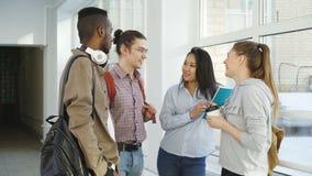 Πολυ-εθνική ομάδα τεσσάρων σπουδαστών που στέκονται στην ευρεία lighty υαλώδη αίθουσα στο κολλέγιο που μιλά ο ένας στον άλλο με τ απόθεμα βίντεο