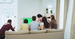 Πολυ εθνική ομάδα φίλων που κουβεντιάζουν καθμένος στον καναπέ σε ένα ευρύχωρο καθιστικό και προσέχοντας έναν αγώνα ποδοσφαίρου απόθεμα βίντεο