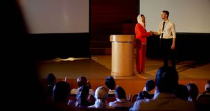 Πολυ-εθνικοί επιχειρηματίες που τινάζουν το χέρι στη σκηνή στο επιχειρησιακό σεμινάριο στην αίθουσα συνεδριάσεων 4k απόθεμα βίντεο