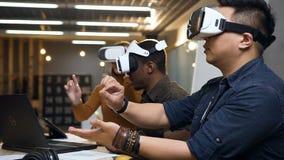 Πολυ εθνικός εργαζόμενος τρία που εργάζεται με τα γυαλιά εικονικής πραγματικότητας vr στο σύγχρονο γραφείο φιλμ μικρού μήκους