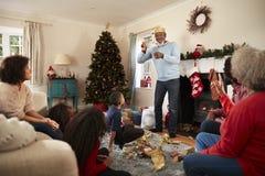 Πολυ οικογενειακό παίζοντας παιχνίδι παραγωγής των συλλαβόγριφων δεδομένου ότι γιορτάζουν τα Χριστούγεννα στο σπίτι από κοινού στοκ εικόνες