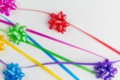 Πολυ τόξα περικαλυμμάτων δώρων χρώματος με τις διεσπαρμένες κορδέλλες ταιριάσματος στο άσπρο υπόβαθρο στοκ εικόνες