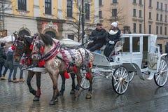 ΠΟΛΩΝΙΑ, ΚΡΑΚΟΒΙΑ - 1 ΙΑΝΟΥΑΡΊΟΥ 2015: Μεταφορές αλόγων στο oldtown σε μια πρώτη ημέρα του νέου έτους 2015 στοκ εικόνες