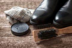Πολωνική κρέμα, βούρτσα, βρώμικο ύφασμα και μαύρη μπότα Στοκ Φωτογραφίες