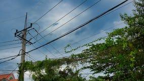 Πολωνός για τις αστικές γραμμές επικοινωνιών, ηλεκτροφόρα καλώδια, πράσινη βλάστηση, συννεφιάζω ουρανός στοκ φωτογραφίες με δικαίωμα ελεύθερης χρήσης