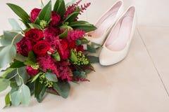 Πολύβλαστη νυφική ανθοδέσμη των κόκκινων τριαντάφυλλων και πολλής πρασινάδας με τα κομψά νυφικά παπούτσια γάμος Στοκ Εικόνες