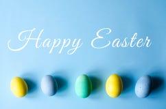 Πολύχρωμα αυγά Πάσχας σε ένα μπλε υπόβαθρο στοκ εικόνες