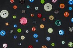 Πολύχρωμα και διάφορα κουμπιά μεγέθους στο σκοτεινό υπόβαθρο στοκ φωτογραφίες