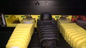 Πολύχρωμα καλώδια δικτύων που παρεμβάλλονται στην επιτροπή δρομολογητών σε ένα σκοτεινό υπόβαθρο Σύνδεση στο Διαδίκτυο, βιομηχανί απόθεμα βίντεο