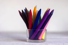 Πολύχρωμα πολύχρωμα μολύβια διαφανή σε έναν γυαλί/γυαλί σε έναν άσπρο ξύλινο πίνακα Στοκ φωτογραφίες με δικαίωμα ελεύθερης χρήσης