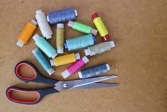 Πολύχρωμα ράβοντας νήματα σε έναν ρόλο για το ράψιμο και την προσαρμογή του ψαλιδιού σε ένα ξύλινο υπόβαθρο στοκ εικόνες με δικαίωμα ελεύθερης χρήσης