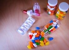 Πολύχρωμα χάπια που ανατρέπουν από ένα μπουκάλι χαπιών σε ένα μουτζουρωμένο κλίμα στοκ εικόνες