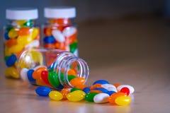 Πολύχρωμα χάπια που ανατρέπουν από ένα μπουκάλι χαπιών σε ένα μουτζουρωμένο κλίμα στοκ φωτογραφία με δικαίωμα ελεύθερης χρήσης