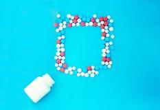Πολύχρωμα χάπια στο μπλε υπόβαθρο με το διάστημα αντιγράφων στοκ φωτογραφίες