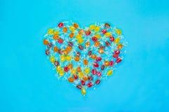 Πολύχρωμες διαμορφωμένες καρδιά καραμέλες με το ζωηρόχρωμο υπόβαθρο στοκ φωτογραφία