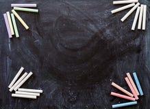 Πολύχρωμες κιμωλίες για το σχέδιο κοντά σε έναν μαύρο πίνακα Στοκ φωτογραφία με δικαίωμα ελεύθερης χρήσης