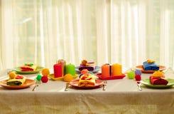 Πολύχρωμες πιάτα και πετσέτες λινού με το πλεκτό ντεκόρ πίνακας στοκ φωτογραφίες