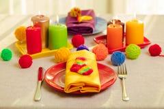 Πολύχρωμες πιάτα και πετσέτες λινού με το πλεκτό ντεκόρ πίνακας στοκ φωτογραφία με δικαίωμα ελεύθερης χρήσης