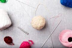 Πολύχρωμες πλέκοντας σφαίρα και βελόνες στο γκρίζο υπόβαθρο Τοπ όψη διάστημα αντιγράφων Πλέκοντας νήμα Στοκ Εικόνα
