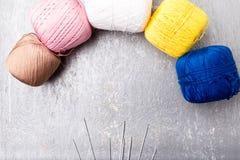 Πολύχρωμες πλέκοντας σφαίρα και βελόνες στο γκρίζο υπόβαθρο Τοπ όψη διάστημα αντιγράφων Πλέκοντας νήμα Στοκ Φωτογραφία