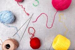 Πολύχρωμες πλέκοντας σφαίρα και βελόνες στο γκρίζο υπόβαθρο Τοπ όψη διάστημα αντιγράφων Πλέκοντας νήμα Στοκ εικόνες με δικαίωμα ελεύθερης χρήσης