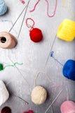 Πολύχρωμες πλέκοντας σφαίρα και βελόνες στο γκρίζο υπόβαθρο Τοπ όψη διάστημα αντιγράφων Πλέκοντας νήμα Στοκ Εικόνες