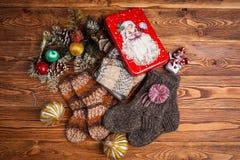 Πολύχρωμες πλεκτές κάλτσες μωρών, διακοσμήσεις Χριστουγέννων και ένα κιβώτιο μετάλλων με την εικόνα Άγιου Βασίλη σε ένα ξύλινο υπ στοκ εικόνα με δικαίωμα ελεύθερης χρήσης