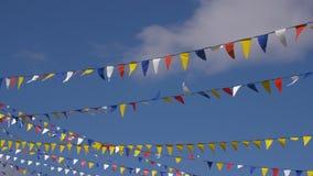 Πολύχρωμες σημαίες τριγώνων για το κόμμα που κυματίζει στον αέρα στο υπόβαθρο μπλε ουρανού Πιάτο υποβάθρου, βασικό βίντεο χρώματο φιλμ μικρού μήκους
