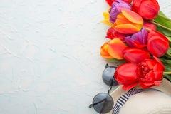 Πολύχρωμες τουλίπες με ένα καπέλο, γυαλιά, σε ένα ελαφρύ υπόβαθρο, μια τοπ άποψη, με το κενό διάστημα για το γράψιμο ή τη διαφήμι στοκ εικόνες