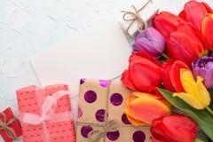 Πολύχρωμες τουλίπες με τα δώρα σε ένα ελαφρύ υπόβαθρο, τοπ άποψη, με το κενό διάστημα για το γράψιμο ή τη διαφήμιση στοκ εικόνες με δικαίωμα ελεύθερης χρήσης