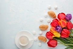 Πολύχρωμες τουλίπες με τον καφέ και croissants και ένα bise σε ένα ελαφρύ υπόβαθρο, τοπ άποψη, με το κενό διάστημα για το γράψιμο στοκ εικόνες