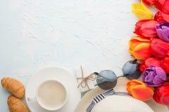 Πολύχρωμες τουλίπες με τον καφέ, καπέλο, γυαλιά, και croissants σε ένα ελαφρύ υπόβαθρο, τοπ άποψη, με το κενό διάστημα για το γρά στοκ φωτογραφίες