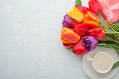 Πολύχρωμες τουλίπες με τον καφέ σε ένα ελαφρύ υπόβαθρο, τοπ άποψη, με το κενό διάστημα για το γράψιμο ή τη διαφήμιση στοκ φωτογραφίες