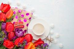 Πολύχρωμες τουλίπες με τον καφέ, τα δώρα και ένα bise σε ένα ελαφρύ υπόβαθρο, τοπ άποψη, με το κενό διάστημα για το γράψιμο ή τη  στοκ εικόνες