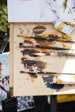 Πολύχρωμες χρώματα και βούρτσες για το σχέδιο, ο εργασιακός χώρος του καλλιτέχνη απεικόνιση αποθεμάτων