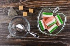 Πολύχρωμη μαρμελάδα στο κύπελλο, teabag, τη ζάχαρη και το φλυτζάνι στοκ εικόνες